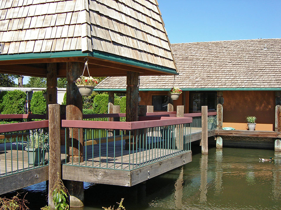 Bridge over pond with covered gazebo halfway. Hanging flower pots and bench to sit on. Duck swimming.