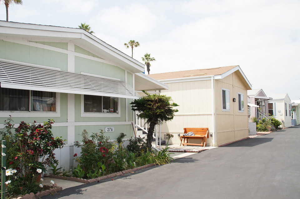 Manufactured home community with clean, paved streets and well maintained landscape. Light, neutral colored homes line the wide streets.