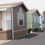 Tan, jade, and baby blue neighboring manufactured homes have a clean exterior and well-maintained landscape. The neutral colors give the community a warm feel.