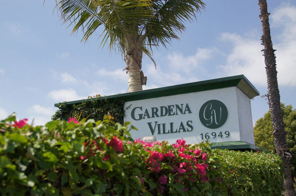 Gardena Villas, a manufactured home community located in Southern California. Greeted by an entrance filled with palm trees, pink and green flowers, and a concrete wall labeled Gardena Villas.