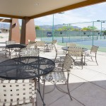 In a partly shady area, tables and chairs sit outside the fenced in pickleball courts