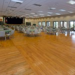 Very large ballroom with a stage and round tables with chairs