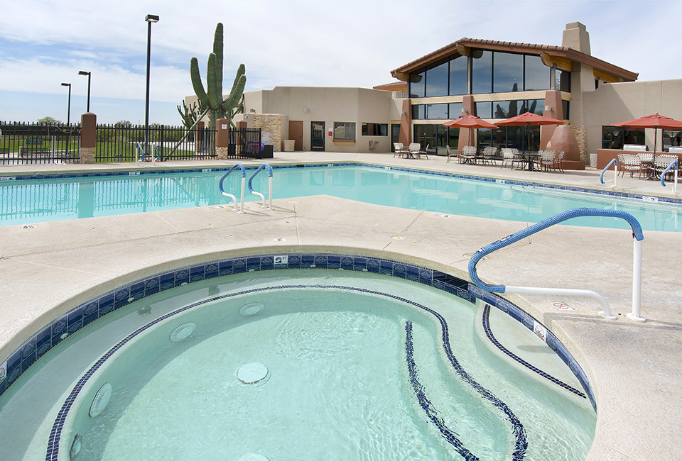 Outdoor pool and jacuzzi. Pool umbrellas and seating on patio and outside clubhouse. Big green cactus planted outside fenced pool area