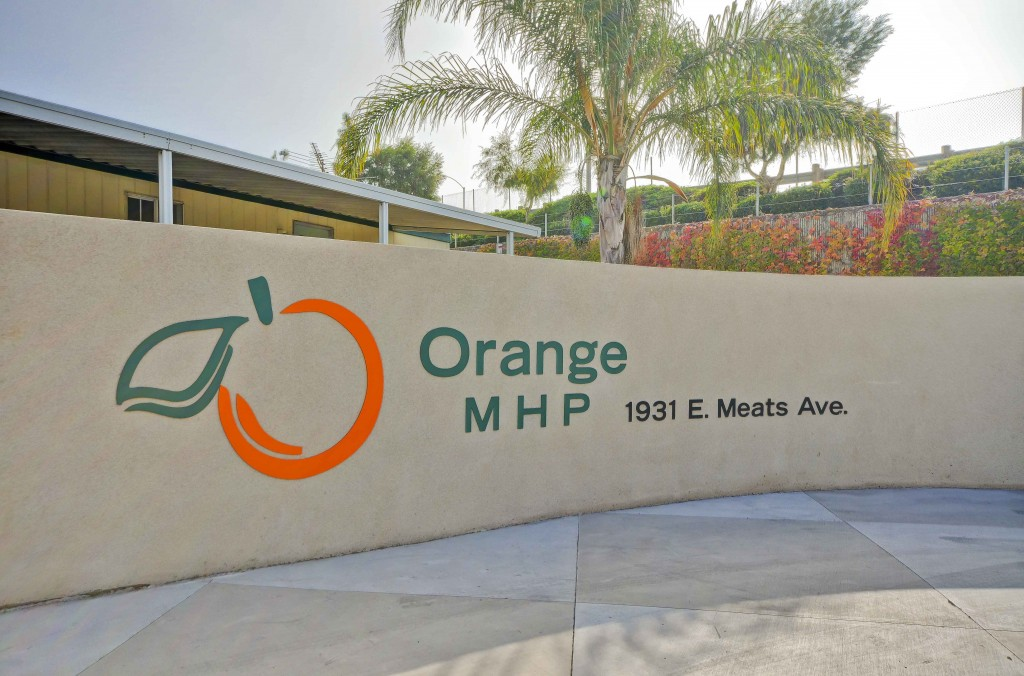 Front Entrance sign to Orange Mobile Home Park, a family community located in Orange County, CA. Green and Orange lettering bring attention the sign.