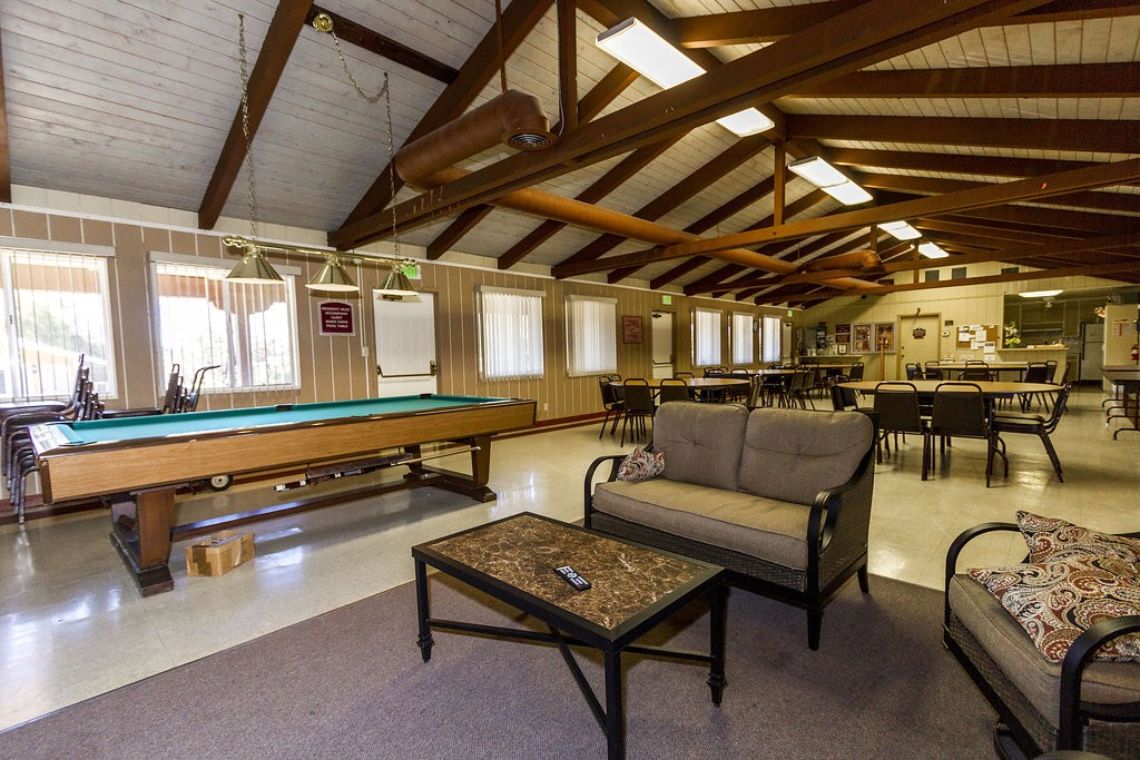 Open community center offers a pool table and an area equipped with couches to lounge at.