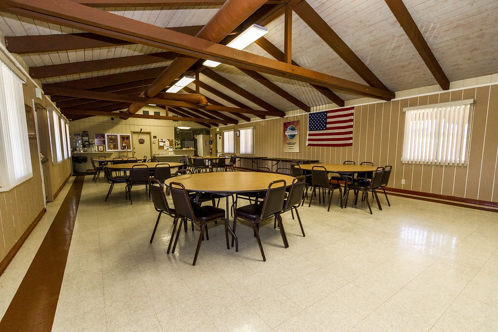 Community center with wood ceiling beams, and tables surrounded with chairs for residents to enjoy an array of activities at.