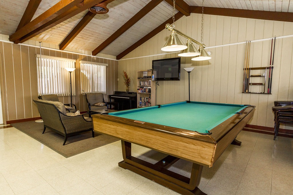 Family style community center offers an area to lounge and relax. Enjoy a book from the bookshelf, either listen to or play the piano, or enjoy a game of pool.