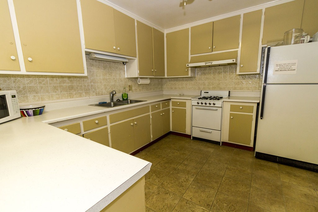 Community center equipped with a full kitchen. Open space with white counter-tops, cream cabinets and beige tile backsplash and flooring.