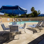 Outdoor community pool provides ample seating arrangements and tables covered with umbrellas to relax outdoors under the shade.