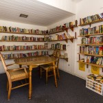 Community library room lined with bookshelves along the walls. Includes multiple books and a seating area for residents to enjoy.