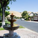 Wide, paved streets create an open space in the 55 plus community. In the foreground a water fountain is surrounded by grass and brick with the beautiful rolling hills behind.