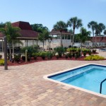 Large Jacuzzi. Two covered cabanas with picnic tables and chairs in the pool area and beautiful landscape with tall palm trees and small shrubs.