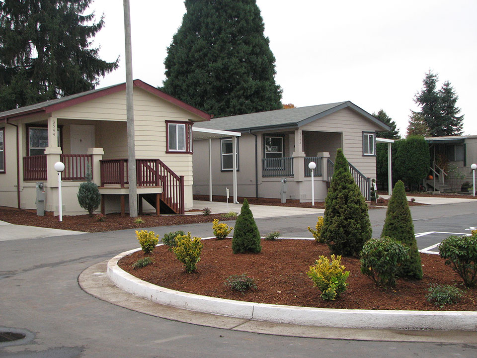 Lakeside Village, an all age manufactured home community with well manicured landscape and lots of tall green trees and shrubs. Well kept homes.