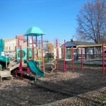 A playground with slides, monkey bars and jungle gym.