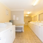 On-site laundry room with washer and dryer hookups, beige tile flooring and cream walls.