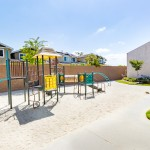 Colorful, outdoor jungle gym surrounded by sand for children to play in.