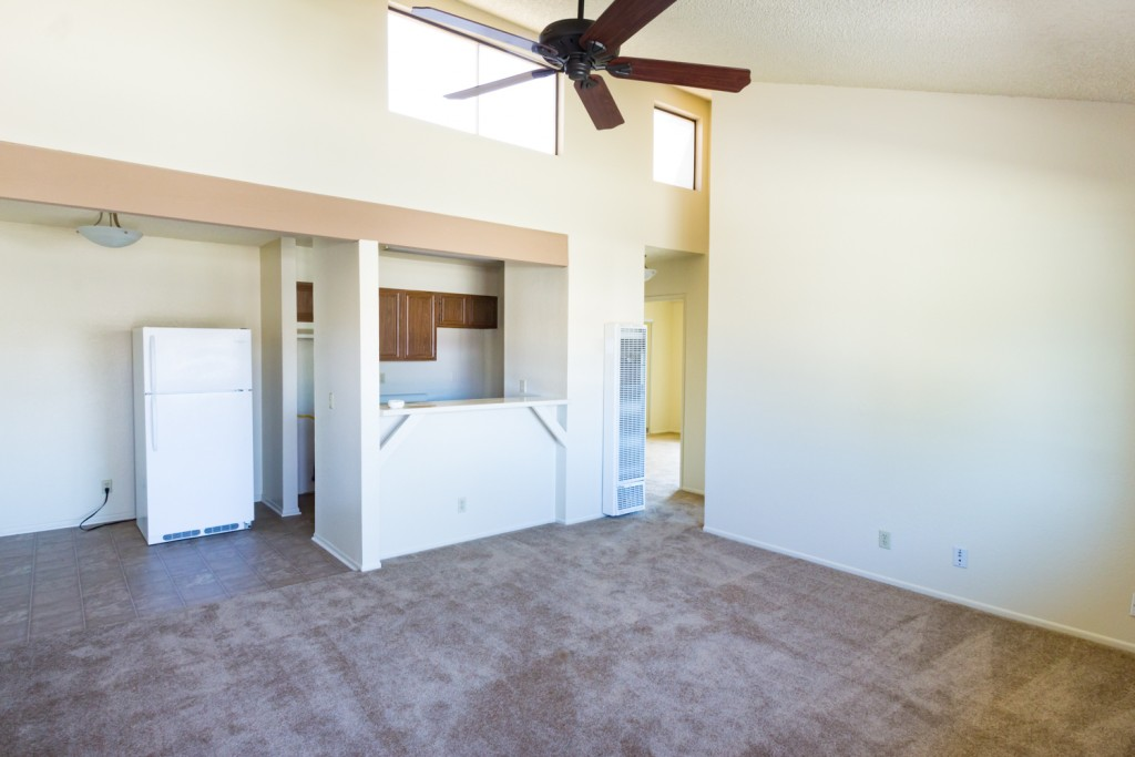 Interior of a unit with high ceilings and windows for natural light. Equipped with ceiling fan and lights, carpet and tile flooring. Open layout with connecting kitchen and living room.