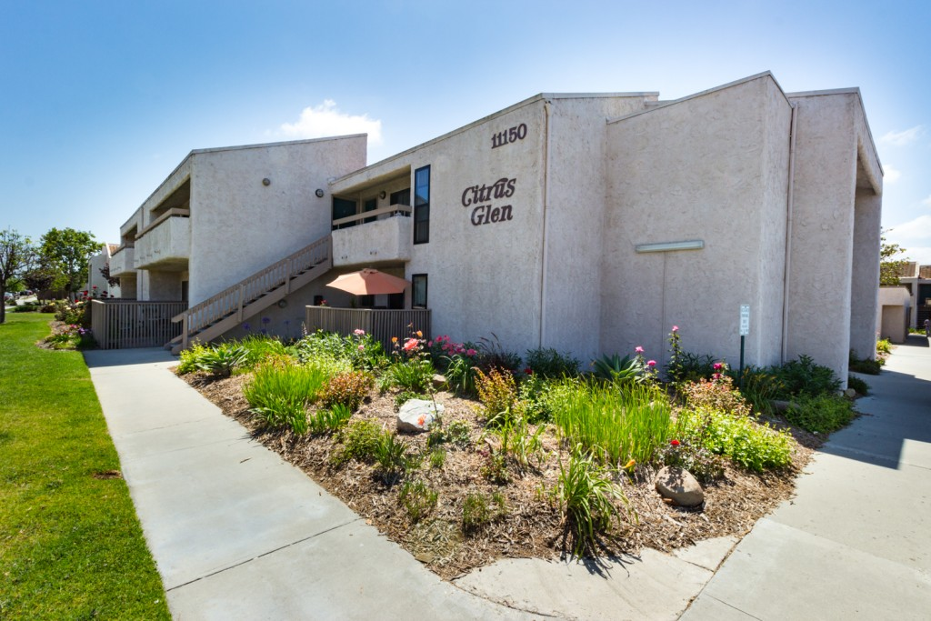 Well-maintained apartment complex with a large Citrus Glen signage on the side wall. In front is a beautiful green landscape filled with flowers, plants, and tanbark.