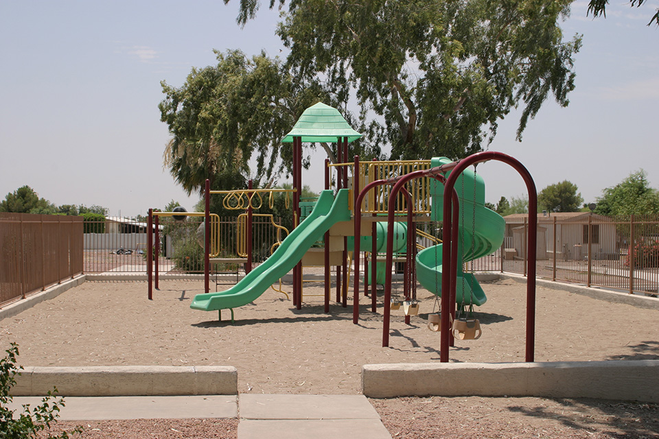 Playground for children with swings, two slides and monkey bars.