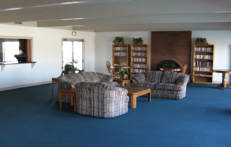 Community center with blue carpet, bookshelves filled with novels, and a three couch lounge area