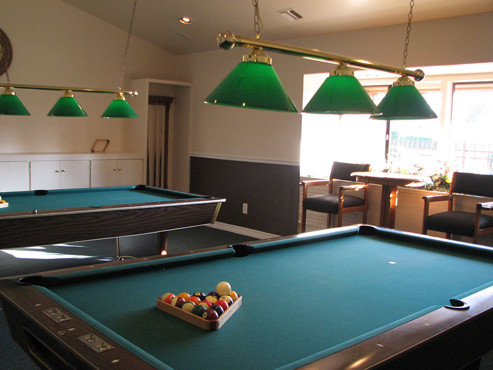 Billiard room with two pool tables. Barstools and table.