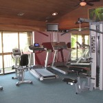 Fitness center with treadmills, stationary bikes, and weight machine.