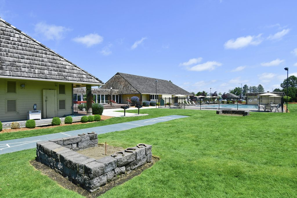 View of the horseshoe pit planted on beautiful green grass, neighboring the clubhouse, office and community pool.