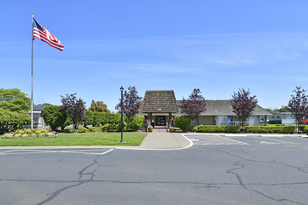 View from the front of the main office and large parking lot. Beautiful green grass and blooming trees and flowers.