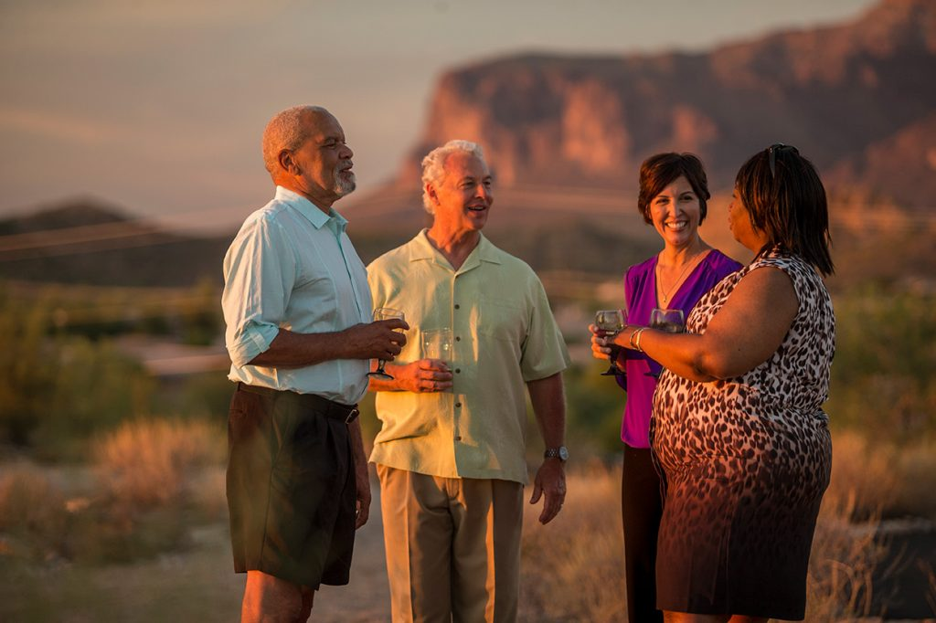 A 55 plus African American man and woman and a older white couple enjoy a cocktail at sunset together standing up with beautiful Superstition Mountains in background