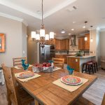 Open floor plan inside beautiful home with wood floors. In Kitchen, stainless steel fridge, oven, microwave and wood cabWood table with seating for 4. Table set with placemats, plates, cups, napkins