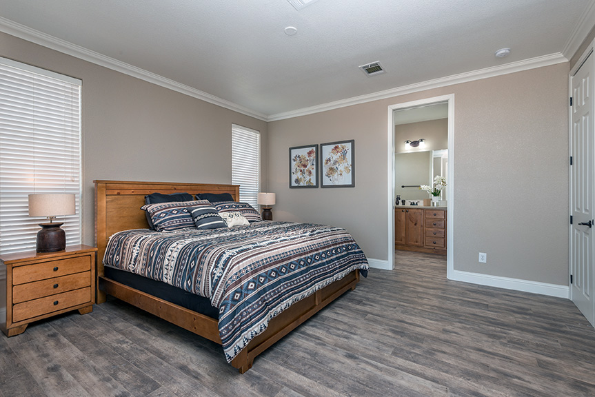 Spacious bedroom with hardwood floors that go through to an attached bathroom. Recessed lighting and crown molding. Large bed with two end tables and 2 lamps.