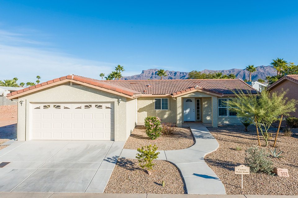 A model home with 2 car garage with small shrubs and rocks as landscape. Smooth walkway to the front door. Superstition Mountain in background.
