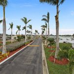 Two wide, paved roads separated by divider with beautiful landscape of plants and palm trees. Entrance roadways are surrounded by palm trees on both sides.