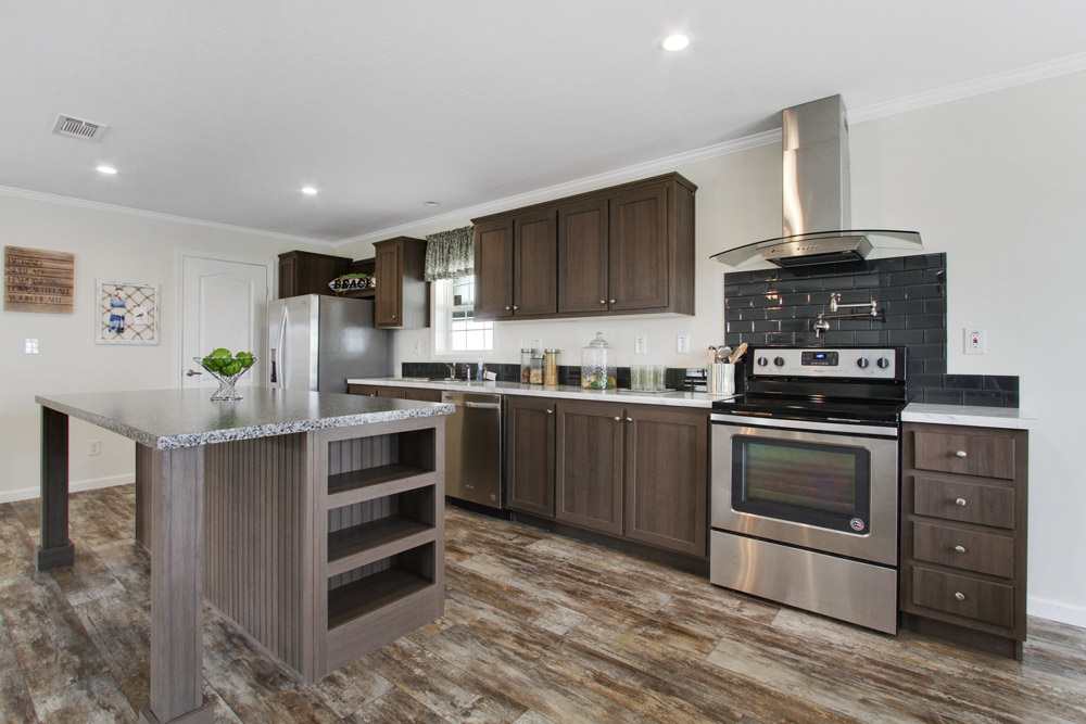 Large, open kitchen layout with counter space and appliances along the wall and large island in the middle. Updated, stainless steal appliances, granite and white counter tops with a dark grey backsplash.