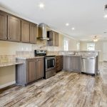 Large, open kitchen with an L-shape layout. Wood cabinets, granite counter tops, beige backsplash, and all stainless steal appliances.