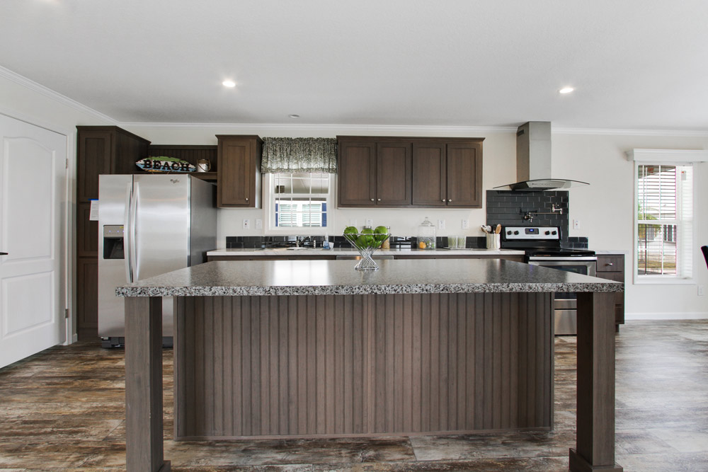 Beautiful updated kitchen with dark wood cabinets, granite counter tops, and stainless steal appliances. Open space with large island in the middle that has attached area for seating.