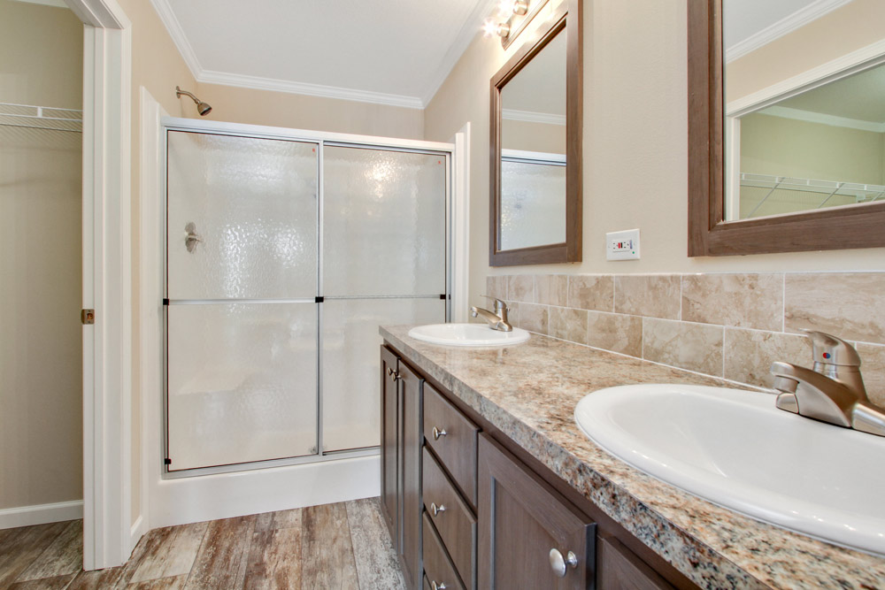 Large bathroom, with his and her sink and mirrors. Granite counter tops, wood cabinets and wood flooring throughout. Includes a stand up shower and walk in closet.