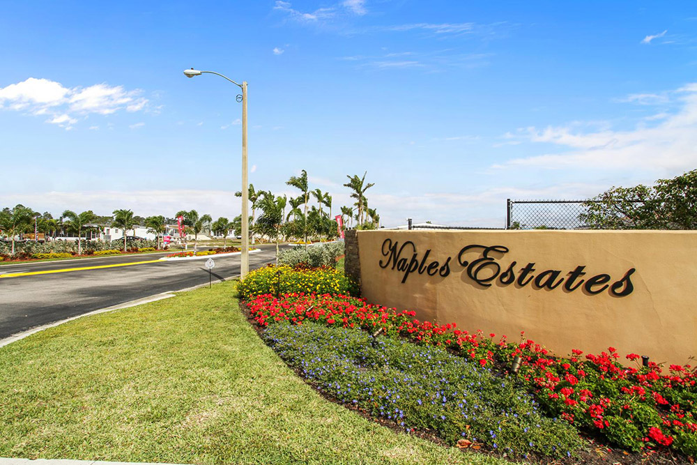 Front entrance to Naples with small, beige-yellow concrete wall with park name written on it. Beautiful landscape surrounds the sign with colorful flowers and clean-cut luscious grass.