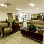 Community center connected to the leasing office with light cream walls and brown bordering. Comfortable seating area for residents to enjoy with a dark wood coffee table surrounded by two individual sofas with a side table and one love seat.
