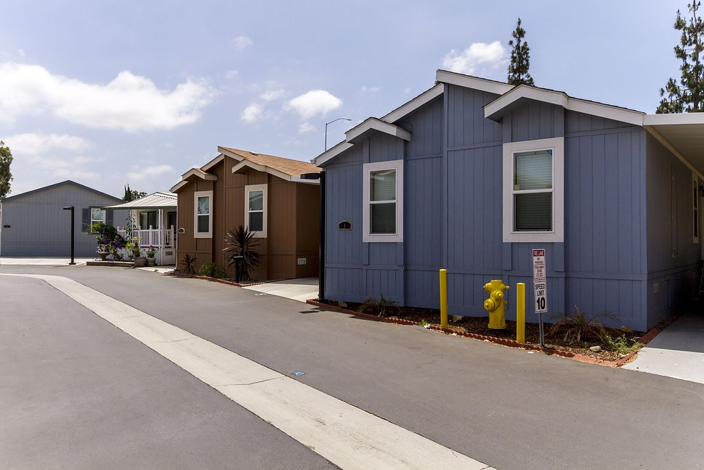 Clean and well maintained manufactured homes line the wide streets. Sky blue colored home sits in the foreground neighboring a tan home and a cream corner home with a front patio.