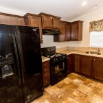 Open kitchen space within a home on the property. Cream tile flooring throughout, wood cabinets, cream granite counter tops, and cream tile backs-plash