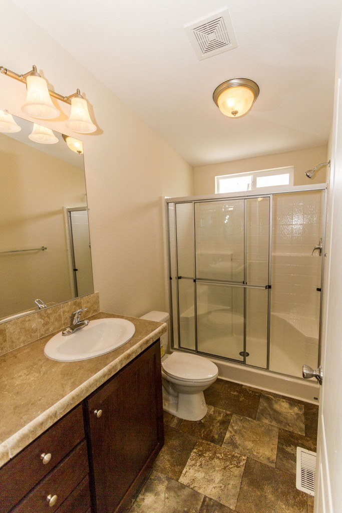 Full bathroom with cream tile-laminate flooring, cream counter tops and single sink with lights above the mirror. Full size walk in shower with single light overhead.