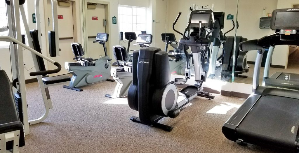 Fitness center with treadmill, stationary bikes, elliptical machine and weight machine.