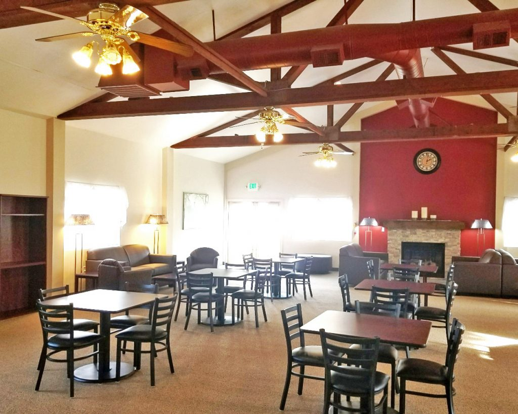 Renovated community room with tables and chairs for seating. Wood beams from ceiling with ceiling fans. Natural light from big windows.