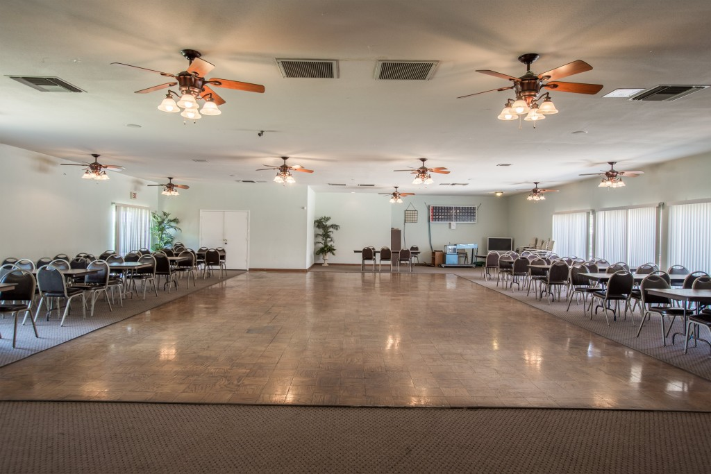 The community room has a dance floor with seating for Bingo times. Nine ceiling fans will help cool off building.