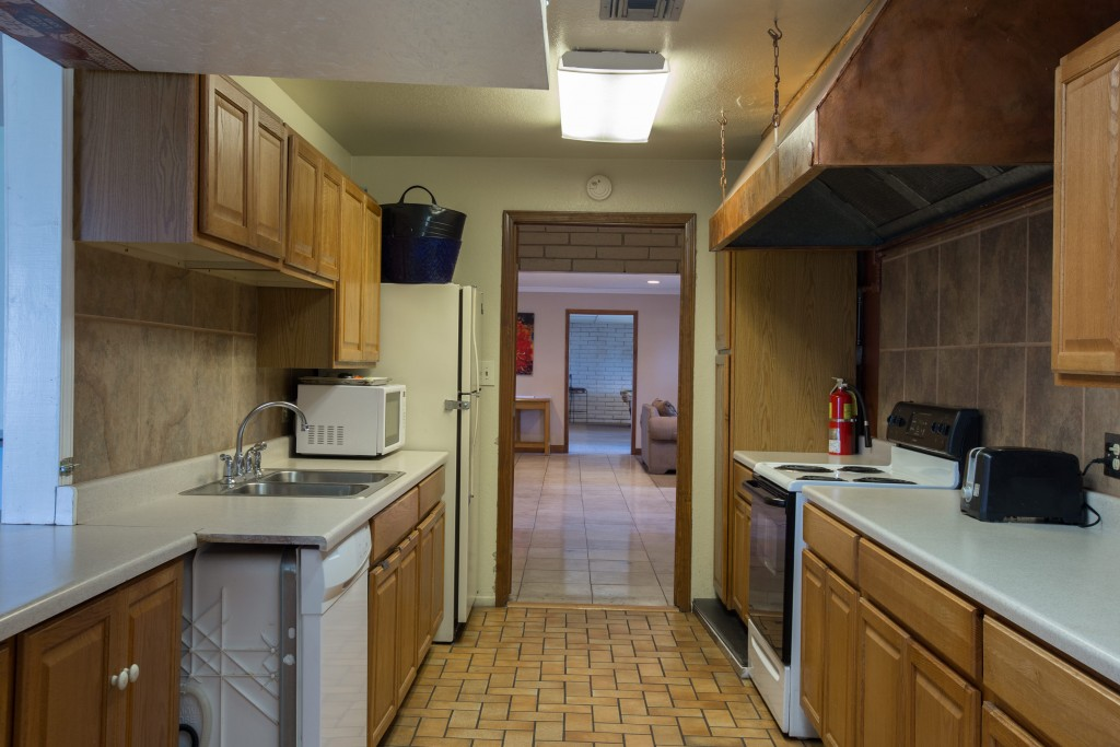 Community room with kitchen. White appliances with dishwasher, fridge, microwave, and oven.