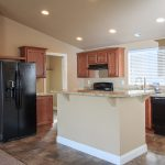 An open kitchen with all black appliances like a fridge, dishwasher and oven. wood cabinets and wood flooring with granite countertops and vaulted ceilings with recessed lighting.