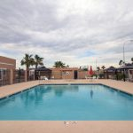 Outdoor heated swimming pool with Cabanas and lounge chairs to relax under. Pool is fenced in.