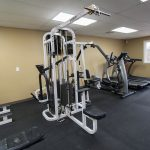 A fitness room with 2 treadmills, elliptical and a weight machine