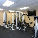 A fitness room with weight machines and flat screen TV on the wall.